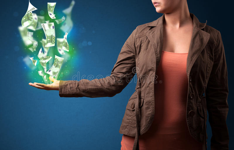 Glowing money in the hand of a woman. Young woman holding glowing paper moneys in her hand royalty free stock photo