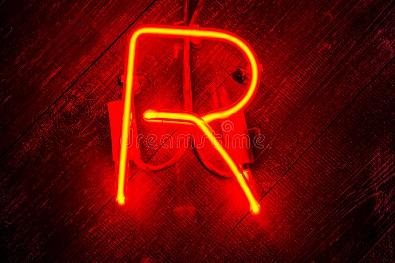Glowing Neon red letter R on wooden background. Dark tones vintage image royalty free stock photo