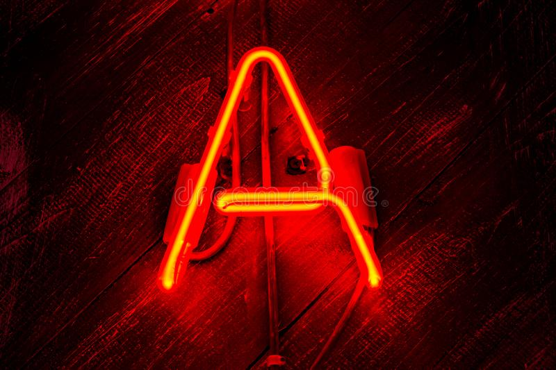 Glowing Neon red letter A on wooden background. Dark tones vintage image stock photos
