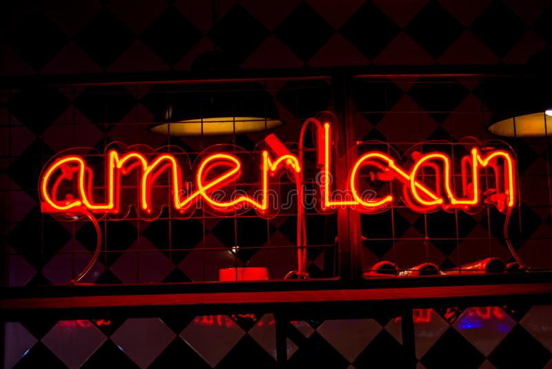 Glowing Neon red sign AMERICAN on dark background. Dark tones vintage image royalty free stock photos