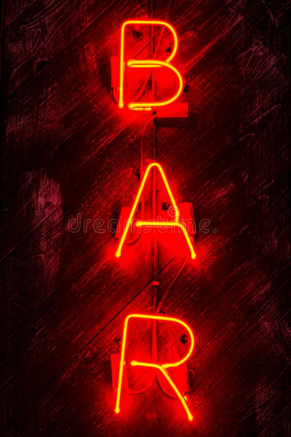 Glowing Neon red  sign BAR on wooden background. Dark tones vintage image stock images