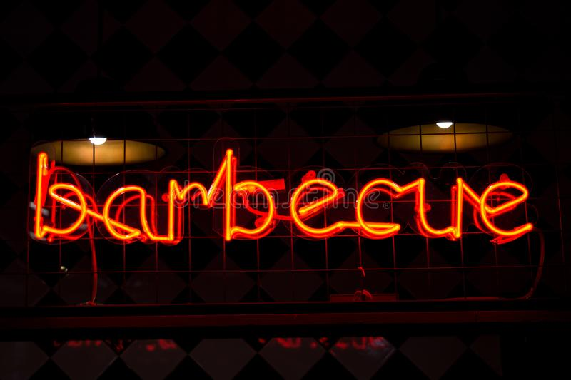 Glowing Neon red sign BARBECUE and blurred lights on black background. Dark tones vintage image stock image