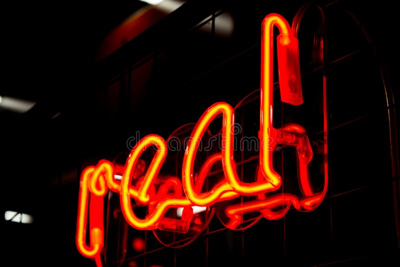 Glowing Neon red sign REAL and blurred lights on black background. Dark tones vintage image stock photo