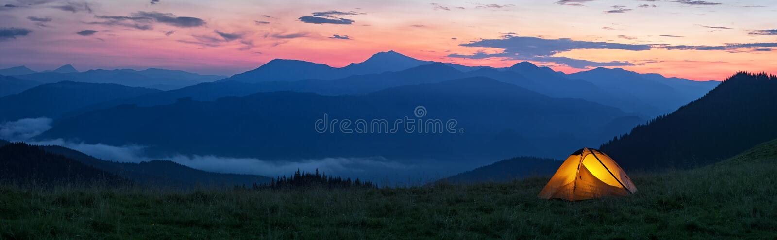 Glowing orange tent in the mountains under dramatic evening sky stock photography