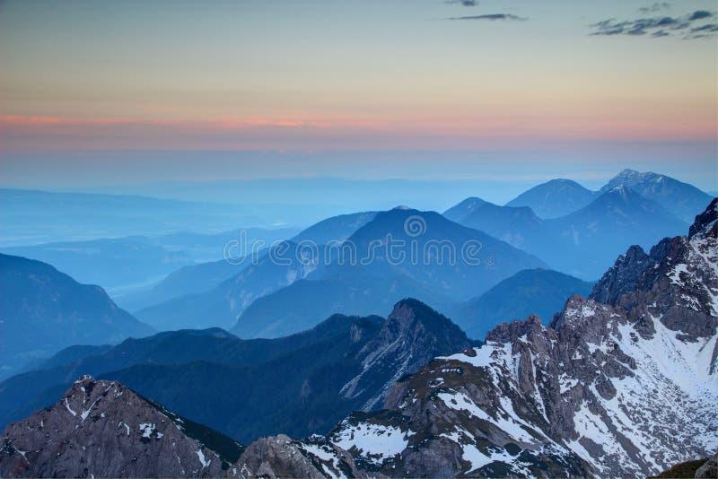 Glowing pink horizon and blue ridges, Karawanken range Austria royalty free stock images
