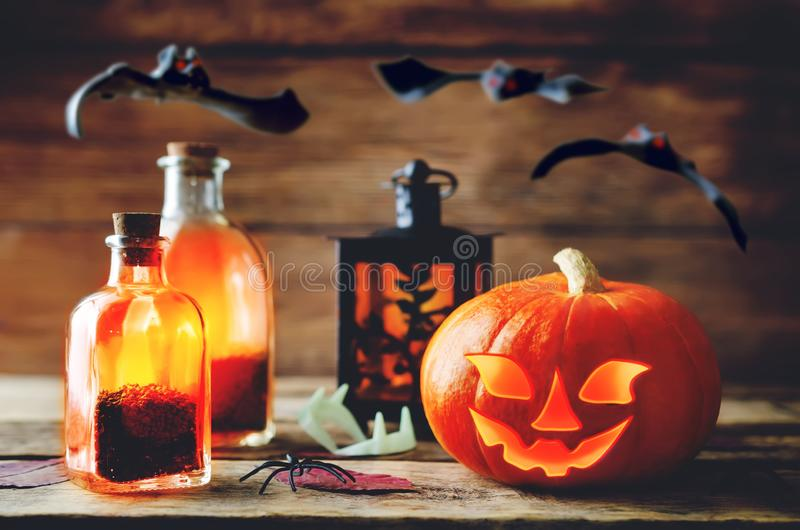 Glowing pumpkin with bats on dark wood background. Halloween con stock photography