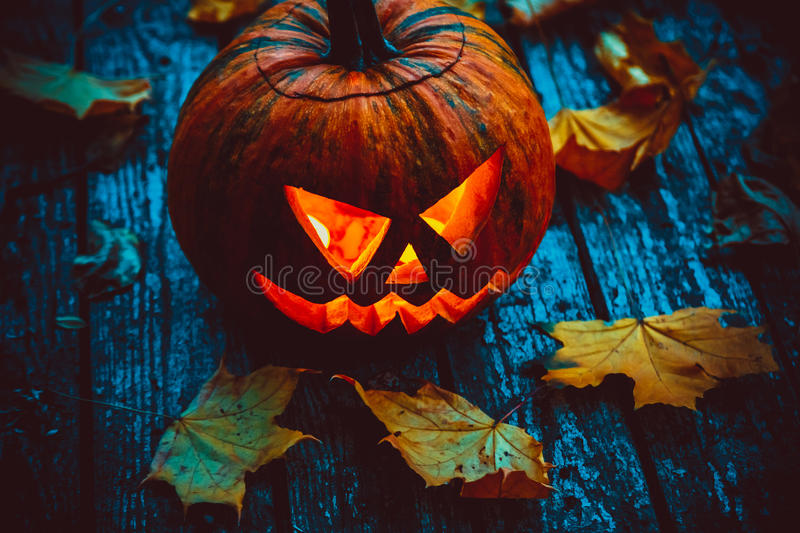 Glowing pumpkin symbolizing the head of old Jack. With autumn leaves on wooden background. Soft focus. shallow DOF royalty free stock photography