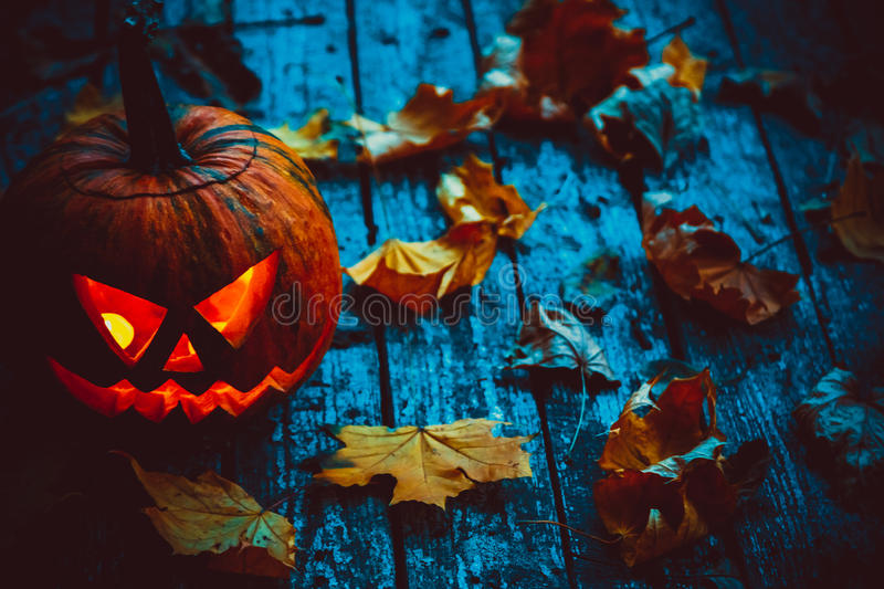 Glowing pumpkins symbolizing the head of old Jack. Glowing pumpkin symbolizing the head of old Jack, with autumn leaves on wooden background. Soft focus. shallow royalty free stock images