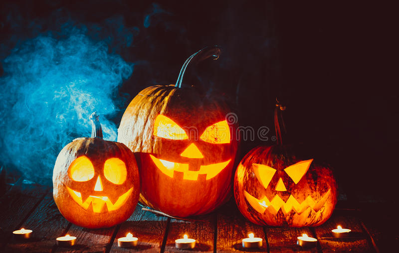 Glowing pumpkins symbolizing the head of old Jack. Three glowing pumpkins symbolizing the head of old Jack, with smoke on wooden background. Soft focus. shallow royalty free stock image