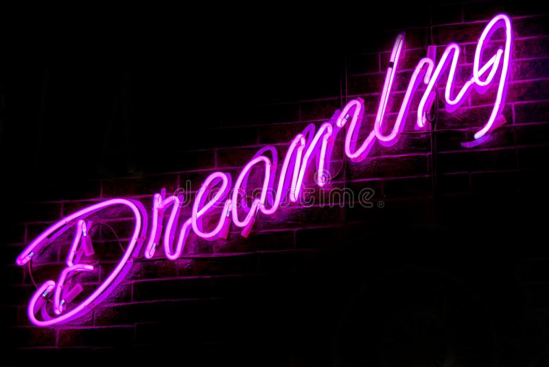 Glowing Purple Neon Inscription DREAMING. On dark brick wall background. Dark tones vintage image stock images