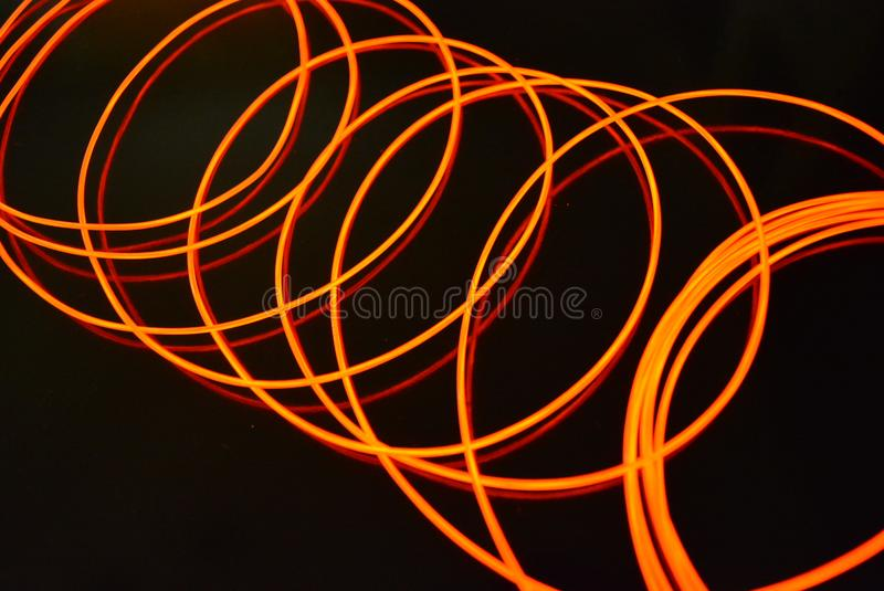 Glowing red material, thin bright threads. Burning wire, beautiful textural drawing of light. Art abstraction light fiber, tangle royalty free stock images