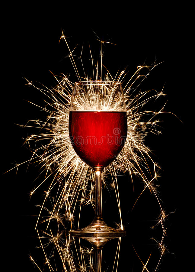 Glowing red wine and firework. Glowing red wine glass and firework on black background royalty free stock image