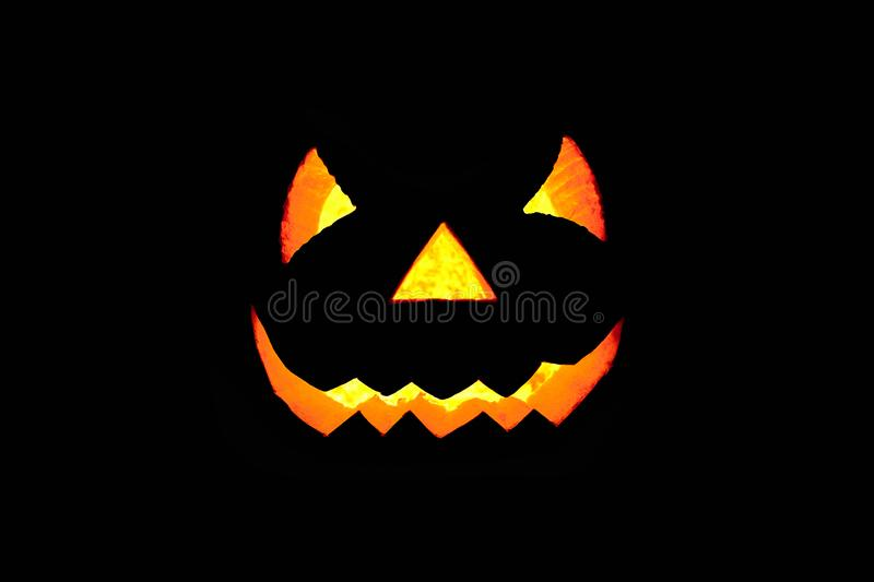 Glowing scary face made of pumpkin on black background. Halloween royalty free stock images