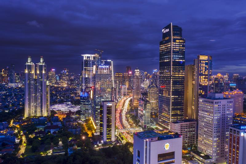 Glowing skyscrapers with hectic traffic at night. JAKARTA - Indonesia. January 03, 2019: Aerial view of glowing skyscrapers with hectic traffic at night time in stock image