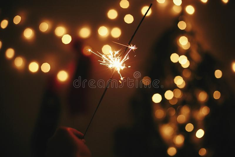 Glowing sparkler in hand on background of golden christmas tree lights, celebration in dark festive room. Happy New Year party. royalty free stock photo