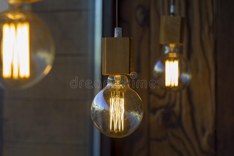 Glowing spherical retro vintage edison incandescent bulbs against a blurred brown wall with a wooden texture and other lamps and stock photos