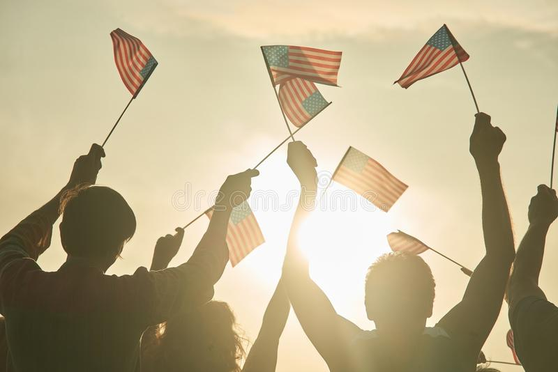 Glowing sun on patriotic american people. Back view people silhouette. USA flags royalty free stock photos