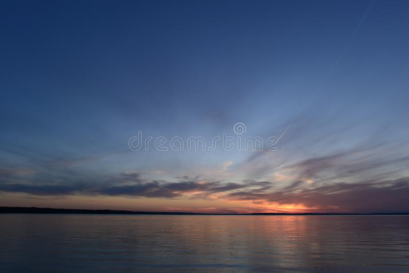 Glowing sunlight in the clear blue twilight sky in the silence of the summer evening before nightfall on a lake royalty free stock photo