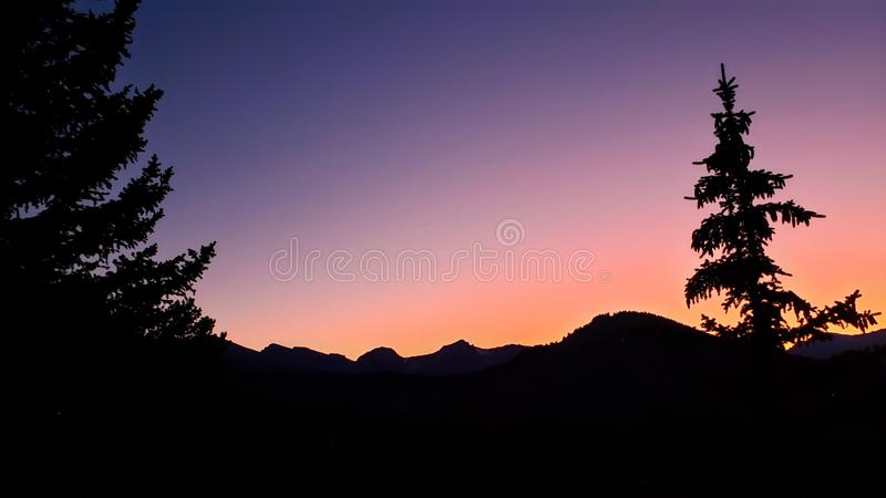 Glowing sunset with mountain and tree silhouette royalty free stock photography