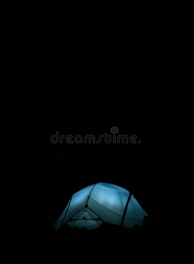 Glowing tent at night while camping stock image