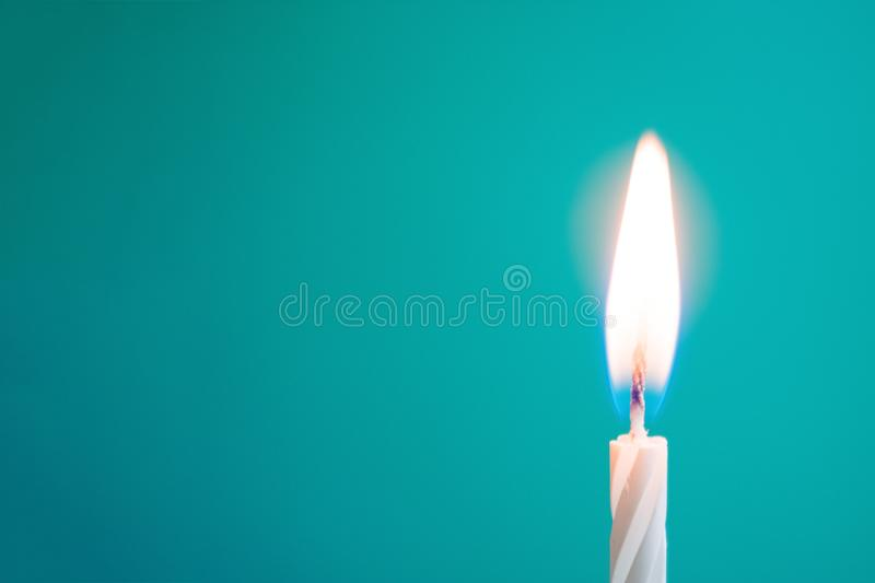Glowing thin white candle on blue background. With copy space royalty free stock photos