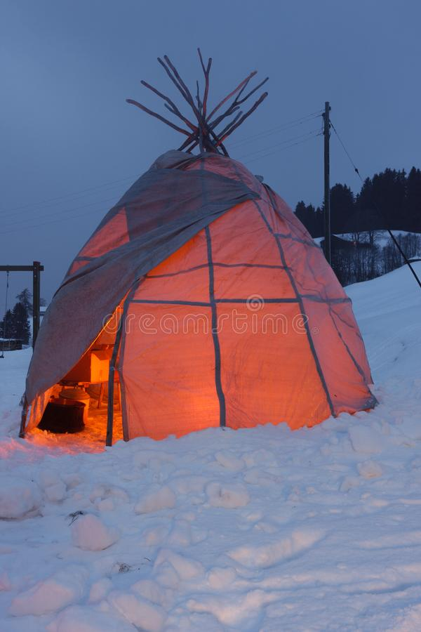 Glowing tipi tent in the snow stock photo