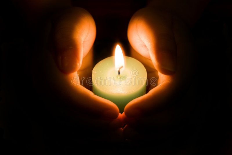 Glowing Warmth. A solitary lit large candle shedding light and glow to a pair of hands encompassing it