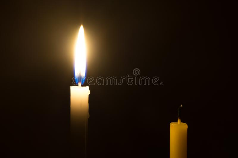 A glowing white candle and a died yellow candle on black background. Two different candles on black background royalty free stock images