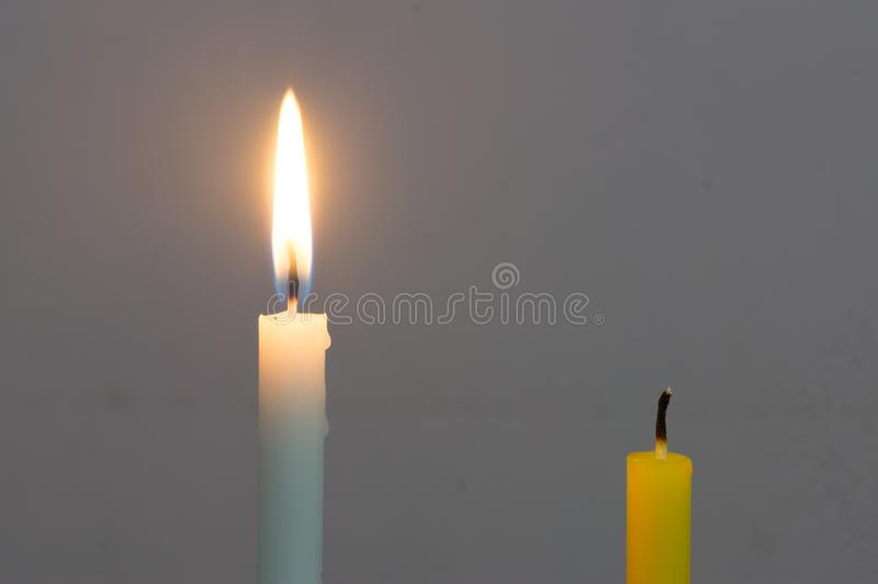 A glowing white candle and a died yellow candle on grey background. Two different candles on grey background royalty free stock images
