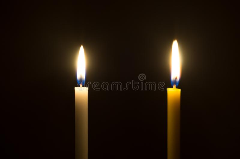 A glowing white candle and a glowing yellow candle on black background. Two color candles glowing on black background royalty free stock photos