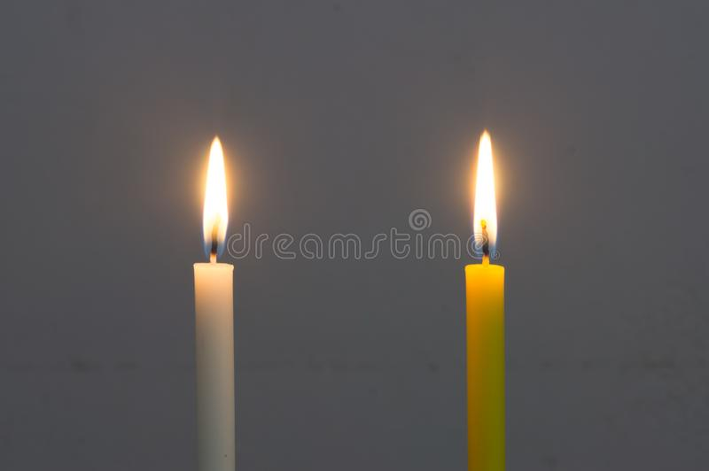 A glowing white candle and a glowing yellow candle on grey background. Two color candles glowing on grey background royalty free stock photography