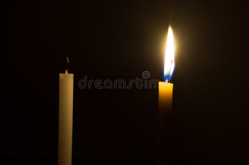 A glowing yellow candle and a died white candle on black background. Two color candles in a dark room royalty free stock image