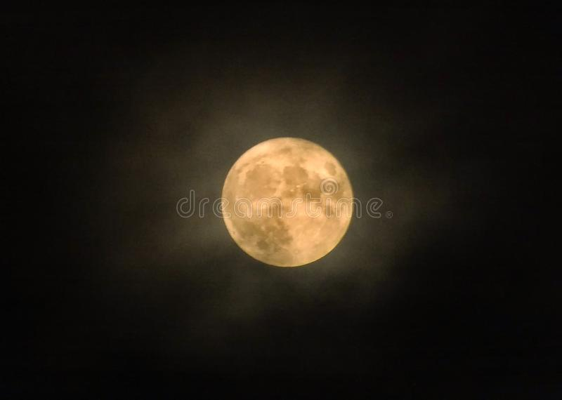 Glowing yellow full winter moon with illuminated clouds royalty free stock images