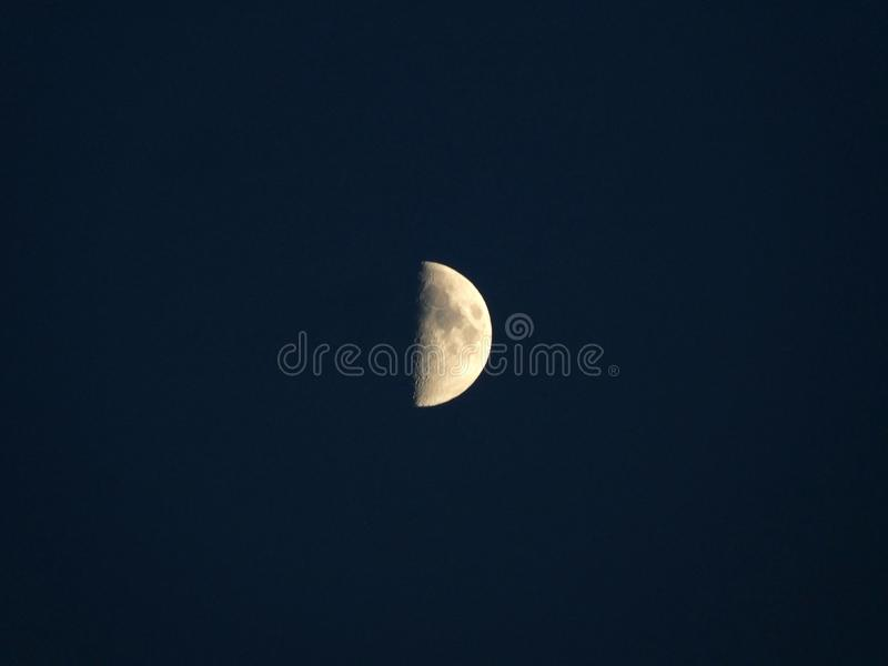 Glowing yellow half moon in a dark blue night sky royalty free stock images