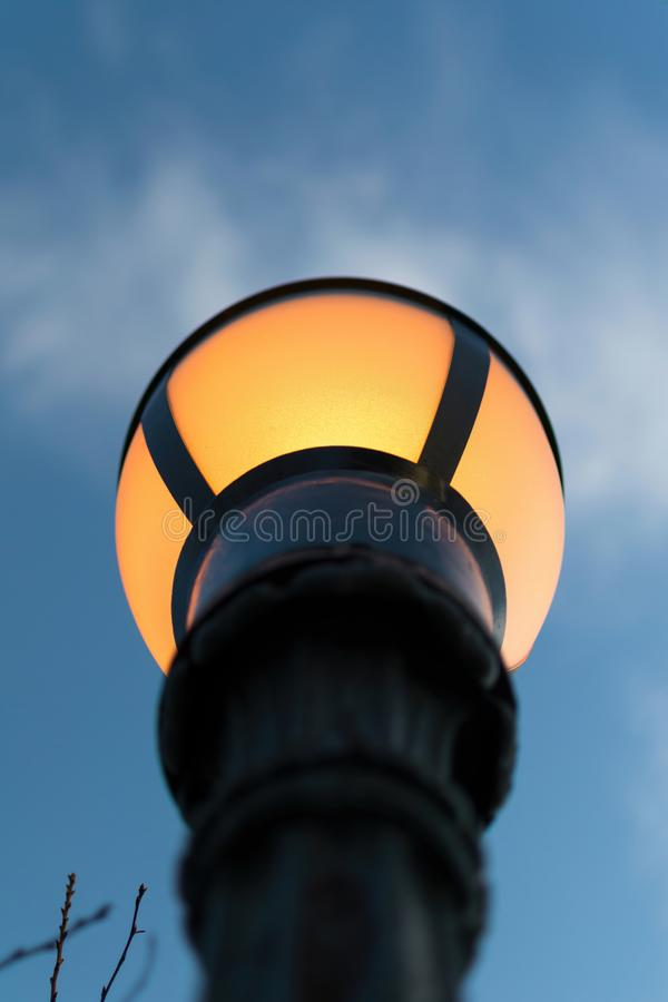 Glowing yellow street lantern, against a blue evening sky stock images