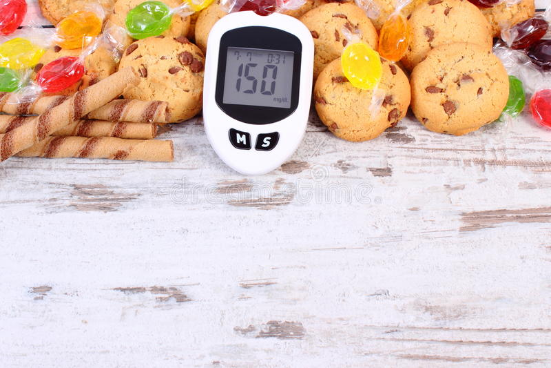 Glucometer和五颜六色的糖果用曲奇饼,糖尿病,吃甜点的减少 库存图片