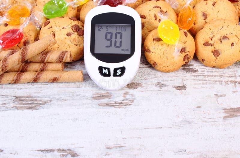 Glucometer和五颜六色的糖果用曲奇饼,糖尿病,吃甜点的减少 库存照片