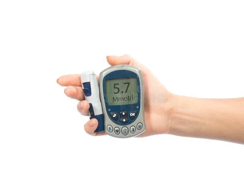 Glucometer在手中评定的葡萄糖级别血液的 库存照片