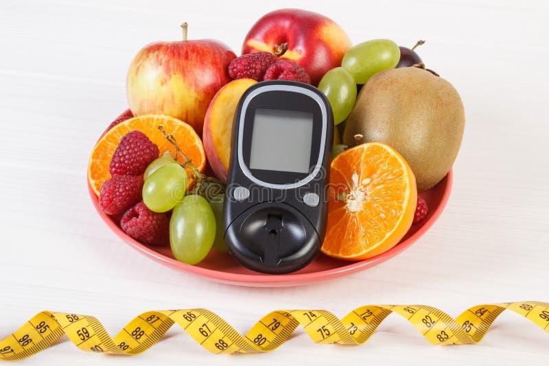 Glucometer, świeże owoc na talerzu, centymetr, cukrzyce i zdrowy odżywianie, fotografia royalty free