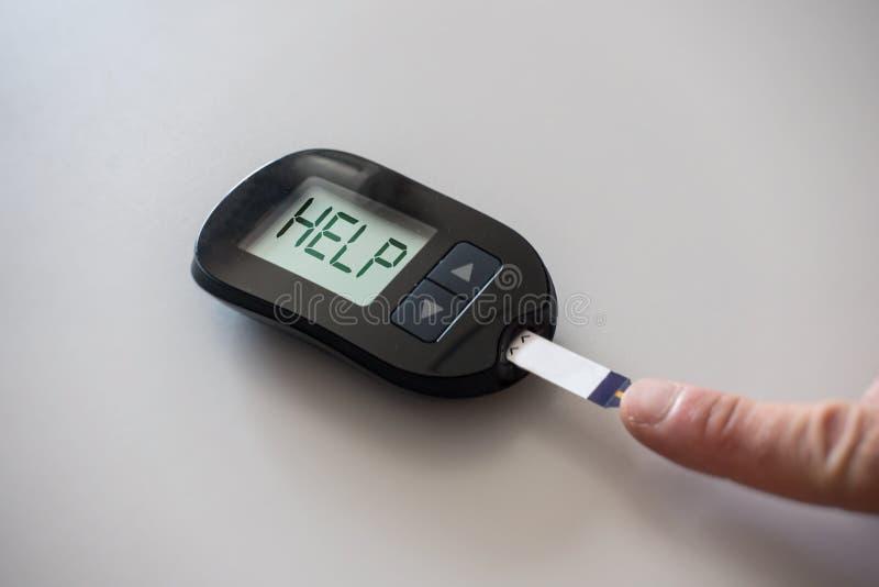 Glucometer просит помощь после измерять уровень сахара в крови стоковое фото