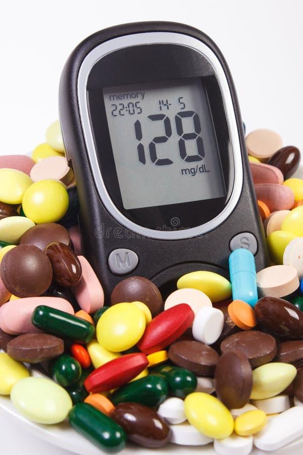 Glucometer avec le niveau de sucre de résultat et le tas des pilules et des capsules médicales, diabète, concept de soins de sant photos stock