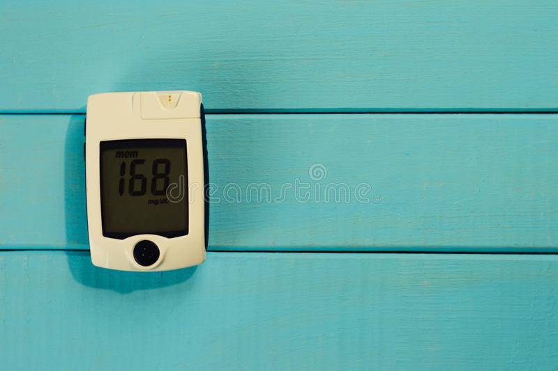 Glucometer on a blue background of sugar in the blood. The concept of diabetes royalty free stock image