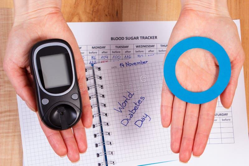 Glucometer e cerchio blu a disposizione, simbolo del diabetico, giornata mondiale del diabete fotografie stock libere da diritti