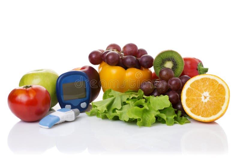 Glucometer för glukosnivå och sund organisk mat royaltyfri bild