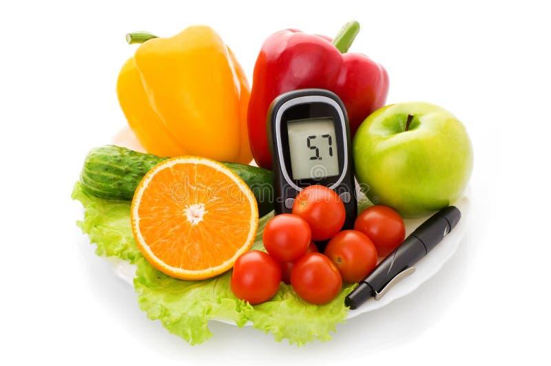 Glucometer für Glukoseniveau und gesundes biologisches Lebensmittel stockbilder