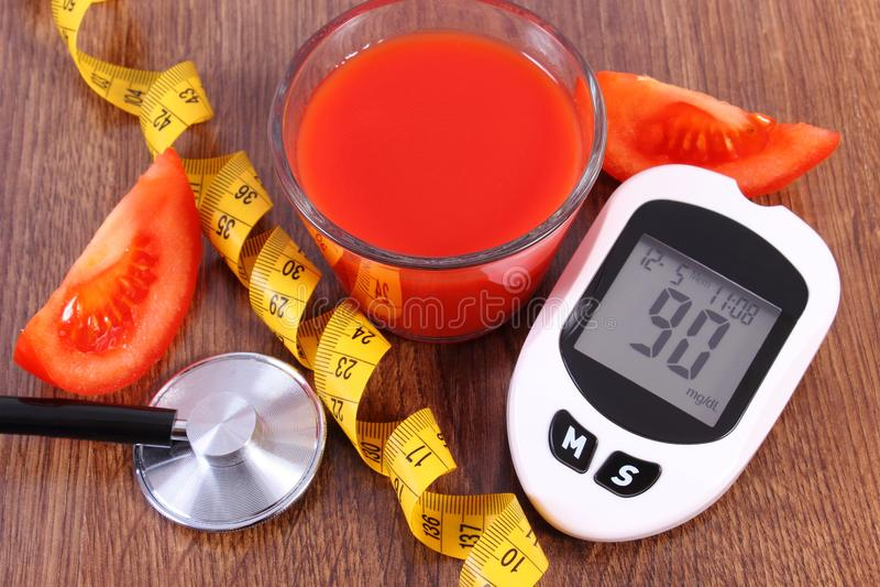 Glucometer für messendes Zuckergehalt mit Zentimeter, frischer Tomate und Tomatensaft, Diabetes, gesundes Nahrungskonzept lizenzfreies stockfoto