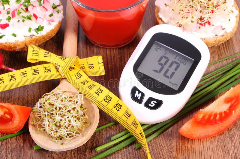 Glucometer, freshly sandwich, tomato juice and centimeter, diabetes, healthy nutrition. Glucose meter with good result sugar level, tape measure and freshly stock photography