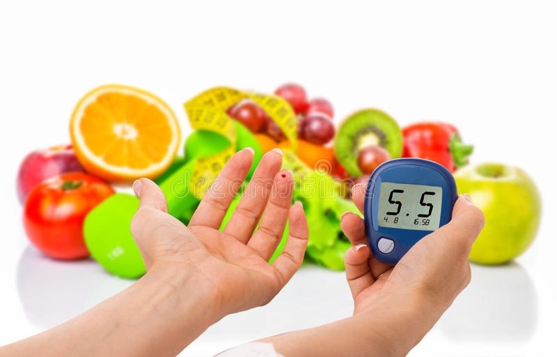 Glucometer for glucose level and healthy organic food on a white background. Diabetes concept. Glucometer for glucose level and healthy organic food on a white stock images