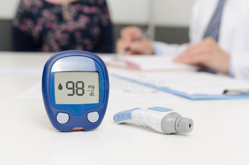 Glucometer and lancet pen. Doctor and patient at office. royalty free stock photography