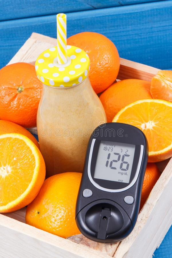 Glucometer mit Zuckergehalt und coctail oder Smoothie von den Zitrusfrüchten Diabetes und gesunder Imbiss, die Mineralien enthalt lizenzfreies stockfoto